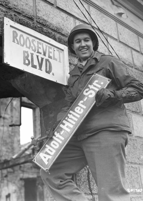 The denazification program in Germany mandated the elimination of Nazi names from public squares, city streets, and other venues. US, Soviet, and British soldiers enthusiastically removed Nazi emblems and renamed public spaces. Krefeld, Germany, March 9, 1945. <i>US Holocaust Memorial Museum, courtesy of National Archives and Records Administration, College Park, MD</i>