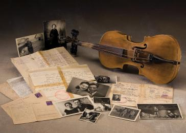 Niusia Gordon's false papers; her parents' marriage registration; photos kept in hiding; postwar photos; three postcards sent to Niusia by her mother, Basia, from the Vilna ghetto; and the violin of Boruch Gordon,who was murdered in 1943 by the Nazis and their collaborators in the Ponary forest near Vilna, Lithuania.