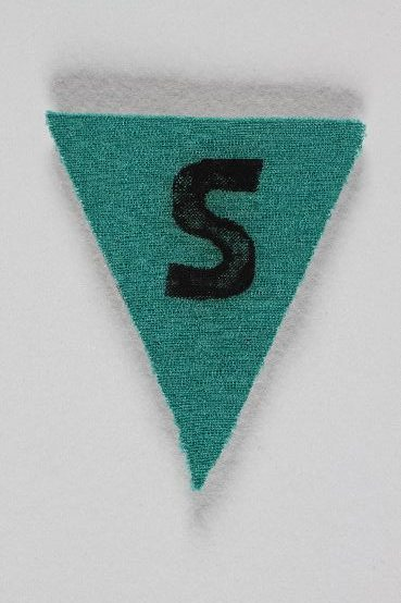 Green badges were used to classify inmates as criminals. This badge, marked with an S for <i>Sicherungsverwahrte</i> (security detainee), was found by a US soldier at the Zwieberge labor camp, a subcamp of Buchenwald. <i> US Holocaust Memorial Museum, gift of National Archives and Records Administration</i>