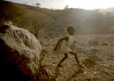 Six-year-old Kuti plays by his grandmother's hut in Sudan's Nuba Mountains.