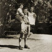 Albanian rescuer Refik Veseli holding the Jewish children he sheltered during the war.