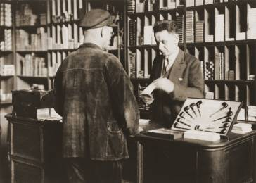 Arthur Lewy confers with a customer in his tobacco shop in Berlin. Arthur and his family endured increasing antisemitic agitation in the years following the Nazi rise to power in 1933. Arthur was arrested in 1938; though he was promptly released, he was soon forced to sell his business. Photograph taken in Berlin, Germany, 1938.