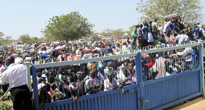 Civilians seeking refuge from the fighting wait outside a compound of the UN mission in South Sudan, December 18, 2013.