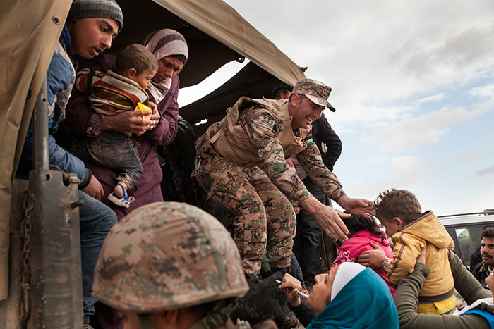 Jordanian troops and UNHCR members provide the refugees with blankets, water, and snacks before helping them onto trucks that will take them to a transit center and then to the Zaatari refugee camp.
