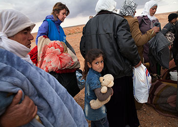 A young Syrian girl clutches her teddy bear as she waits to board a truck to a transit center. The majority of the refugees coming across the Syrian border into Jordan are children.