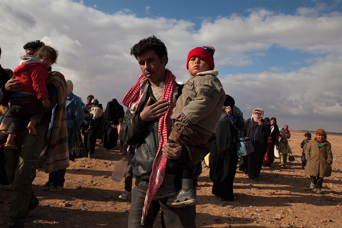 Refugees cross the border from Syria into Jordan