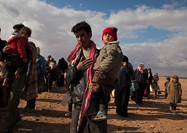 Refugees displaced by the violence in Syria make their way to a transit center in Jordan for trucks that will take them to the Zaatari refugee camp. February 2014.