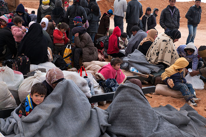 Refugees huddle to keep warm after receiving blankets at a transit center on the Jordanian border. All told, roughly 600,000 refugees from Syria have crossed into Jordan since the civil war began three years ago.