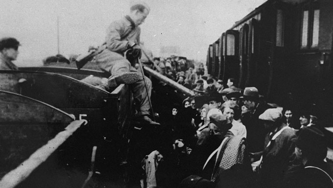 Jews from the Lodz ghetto are forced to transfer to a narrow-gauge railroad at Kolo during deportation to the Chelmno killing center. Kolo, Poland, 1942.
