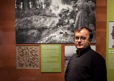 Father Patrick Desbois in the <i>Some Were Neighbors</i> exhibition at the United States Holocaust Memorial Museum. The exhibition features items he has found at killing sites. Washington, DC, April 2014.