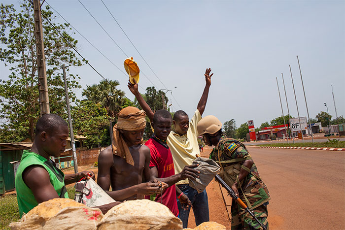 African Union soldiers check civilians for weapons in Bangui. March 2014.