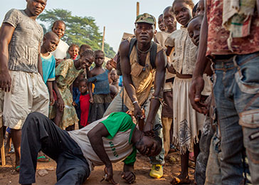 An Anti-Balaka fighter demonstrates a killing technique at the M'Poko IDP camp in Bangui. March 2014.
