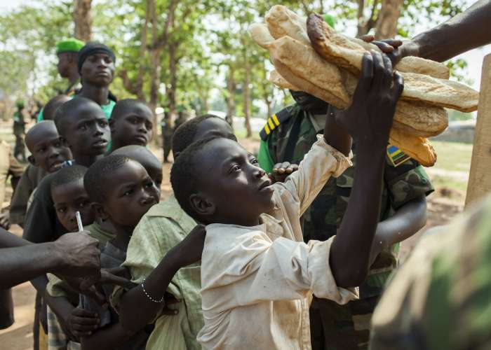 Rwandan African Union soldiers perform <i>Umuganda</i> (Day of Community Service) every Saturday in Bangui just as they do at home in Rwanda. To inspire the locals to participate, the soldiers offer local bread as a reward for their service. March 2014.