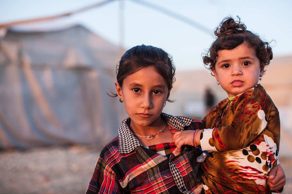 A young Yezidi girl carries her sister in a displaced persons camp in Dohuk, Iraq.