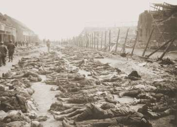 View of the main street of the Nordhausen concentration camp, outside of the central barracks (Boelke Kaserne), where the bodies of prisoners have been laid out in long rows. Nordhausen, Germany, April 13-14, 1945. <i>US Holocaust Memorial Museum, courtesy of Michael Mumma</i>