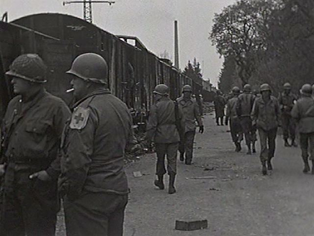 Uniformed men standing in front of train cars