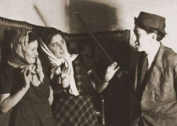 Three young Jews act in a play in the Cernauti ghetto. Erika Neuman is pictured in the center.
