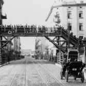 View of Łódź ghetto residents crossing a pedestrian bridge.