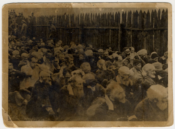 A large group of men seated with their hands on their heads while being forced to watch the execution of Moshe Kagan and Wolf Kieper. Zhitomir, Ukraine.