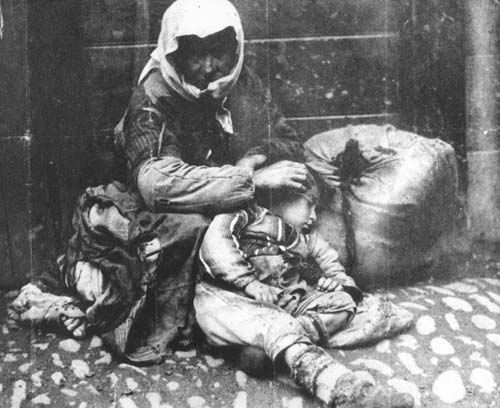An Armenian woman and her child sit on a sidewalk next to a bundle of their possessions. Ottoman Empire, 1918–1920.