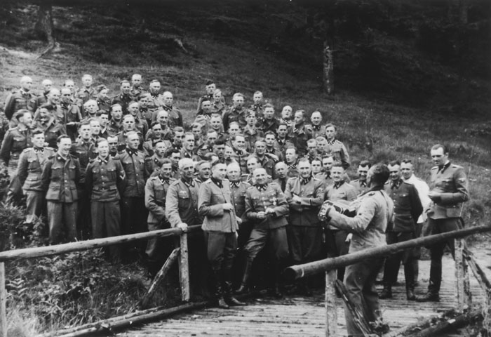 "A ""sing-along"" during a social gathering of the SS hierarchy at Solahütte. The front row consists of (left to right): Karl Höcker, Otto Moll, Rudolf Höss, Richard Baer, Josef Kramer, Franz Hössler, and Josef Mengele."