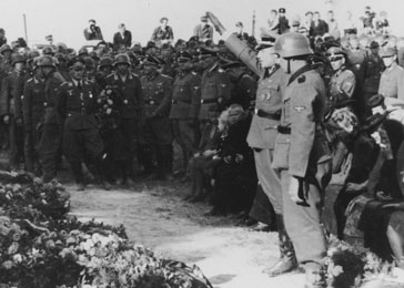 The funeral of SS officers killed in the December 26, 1944, Allied air raid on Auschwitz.  Karl Höcker is giving the Nazi salute in front of a group of mourning women and children.