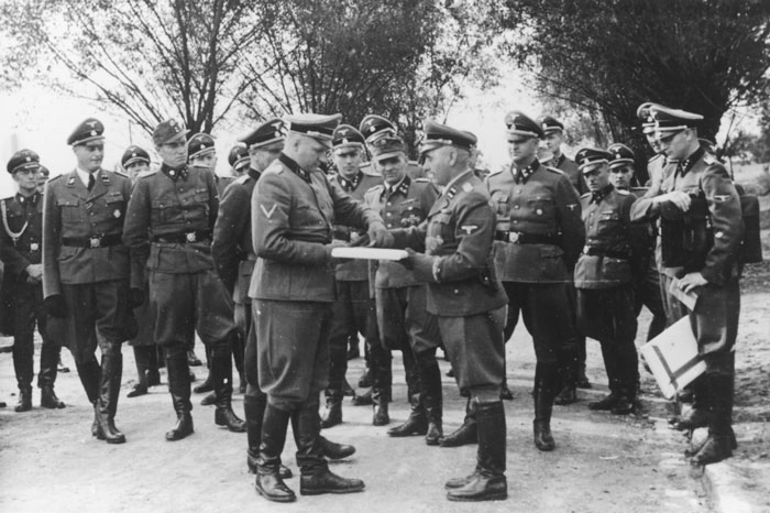 September 1, 1944, Richard Baer ceremonially accepts a copy of the construction plans from the Chief of the Central Construction Directorate of the Waffen SS, SS-Sturmbannführer Karl Bischoff, celebrating the opening of an SS military hospital (SS-Lazarette).