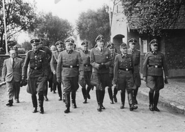 Walking to a ceremony; From left to right: Dr. Carl Clauberg, Dr. Enno Lolling, Karl Höcker (behind), Richard Baer, Dr. Eduard Wirths, Karl Bischoff (behind Wirths on the right) Rudolf Höss, and Karl Möckel.