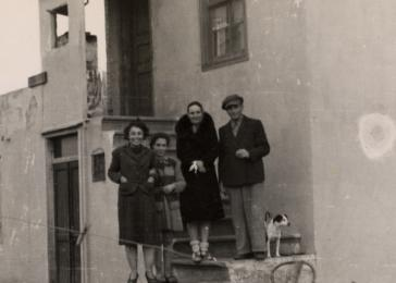 Alice Gerechter, her daughter Johanna Jutta Gerechter, Lizalotte Pilku and Siegbert Gerechter stand on the steps of their home in Albania. The Gerechter family lived in this house from June 1941 to August 1943.