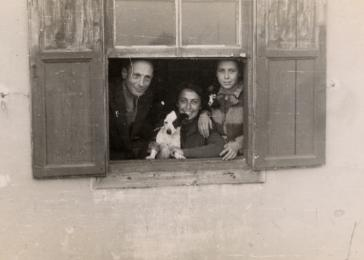 Jewish refugees Siegbert, Alice and Johanna Gerechter look through the window of their one room home in Albania.