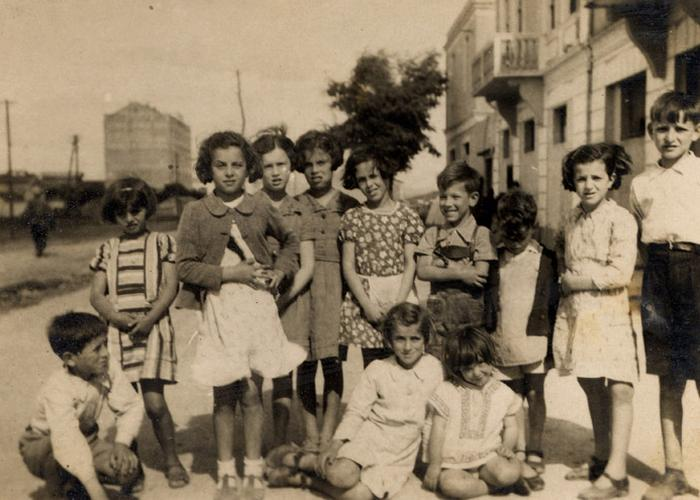 German and Austrian refugee children pose with Albanian children shortly after their arrival. Johanna Gerechter is standing in the center with an apron.