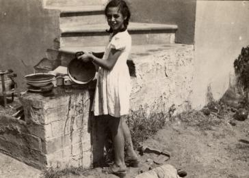 Johanna Jutta Gerechter washes dishes outdoors in Shkoset Albania.