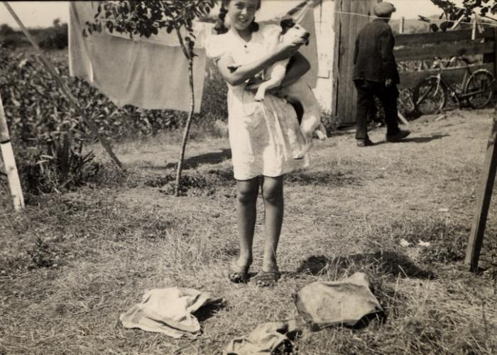 Johanna Jutta Gerechter stands with her dog Piccola next to a laundry line in Albania. Her family was supporting themselves in exile by doing laundry for Italian truck drivers.