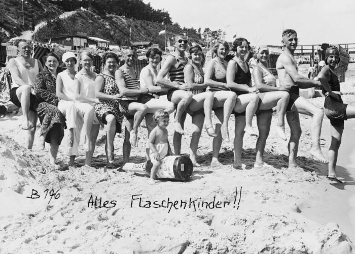 "Friends and relatives of the Glueckstein family on a beach in Germany. Fritz Glueckstein sits in front on an inflatable ""wine bottle""."