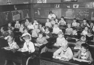 First grade pupils study in a classroom in a public school in Hamburg, Germany, June 1933. Jewish pupil Eva Rosenbaum (with the white collar) is seated in the center desk on the right. On December 12, 1938 Eva left for England on the second <i>Kindertransport</i>.