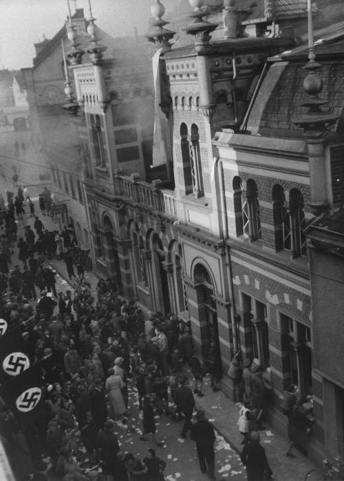 Local residents gather outside the smoldering ruins of the Annaturmstraße  synagogue in Euskirchen on the morning after Kristallnacht.