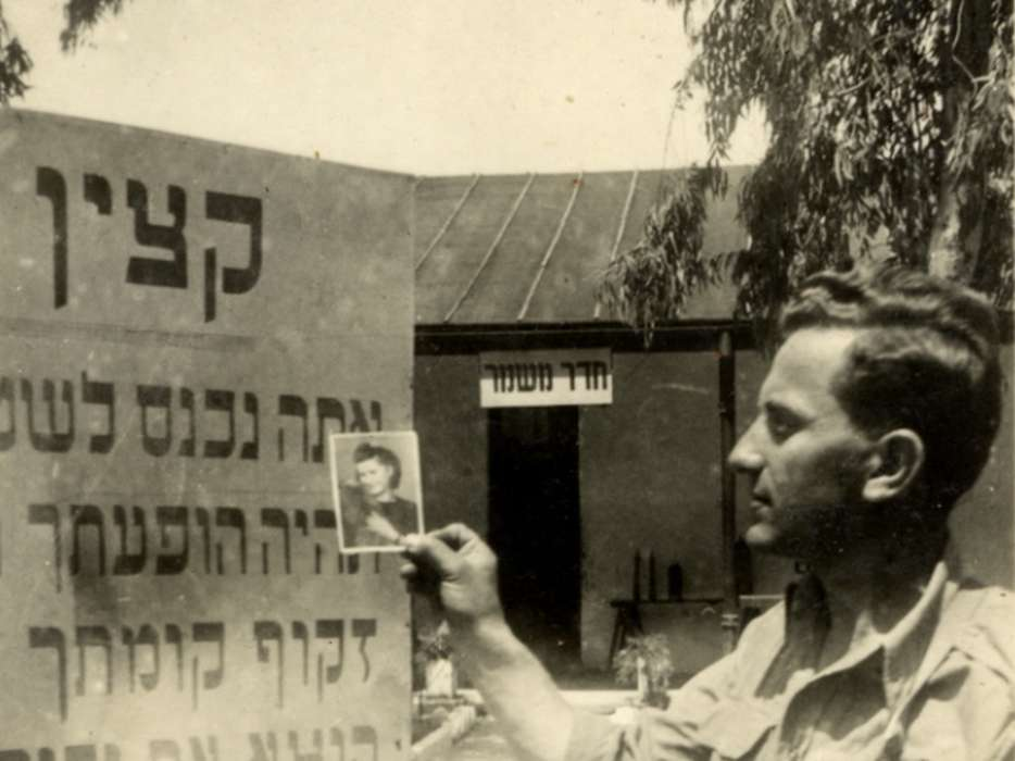 David Bajer holds a photograph of fellow survivor, Regina Spiegel, next to the entryway sign at the army base in Israel where he was stationed during the War of Independence.