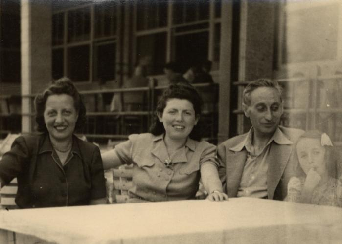 A Jewish family sits at an outdoor table after the war. From left to right are Marta Mandler, Erszi Herzel, Ludwig Engel, and Katie Engel.