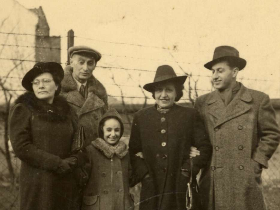 Greta Stoessler Engel, Ludwig Engel, Katie Engel, Marta Mandler and Victor Adler stand by a fence on their farm after the war.