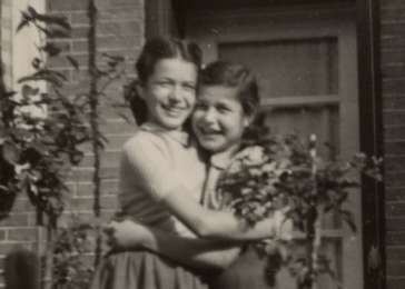 Manuela (left) and Jacqueline Mendels hug each other outside the home of their uncle, Majoor Albert Van Weenen, where they have come after the war to reunite with surviving relatives. Their uncle's wife and daughter both perished in the camps.