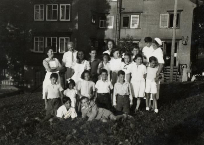 Group portrait of children and staff posing on the grounds of the Heiden children's home in Switzerland. Manny Mandel is pictured on the bottom left. His mother, Ella Mandel, in standing in the back row, center.