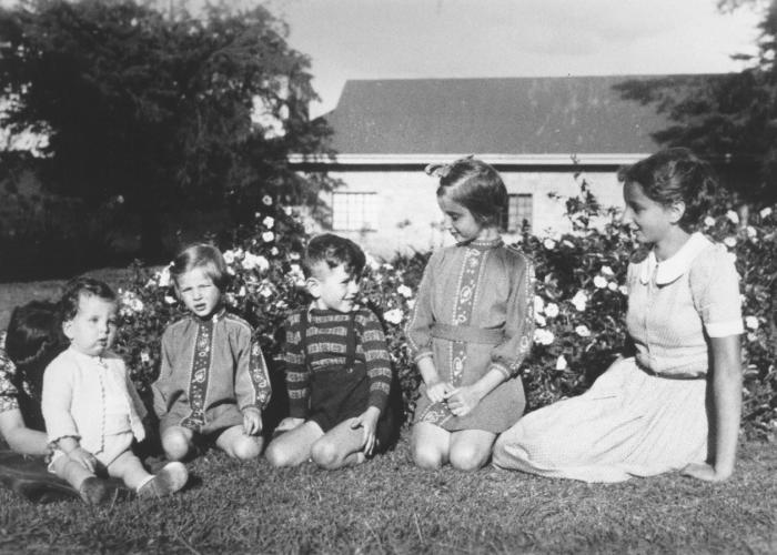 Philip Berg (being supported by his Aunt Erna), Hannah Baum, Egon, Gisela and Inge Berg pose outside on the lawn of their farm near Limuru, Kenya (Kiambu district), where they found refuge during World War II.