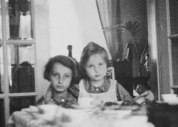 Sisters Gisela and Inge Berg sit together at the dining room table in their parent farmhouse after hearing about the family plans to emigrate from Germany.