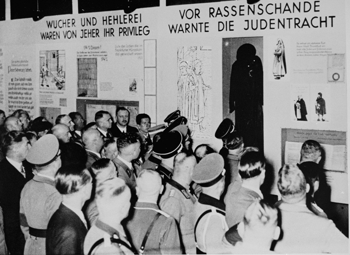 "Nazi officials in attendance at the opening of ""The Eternal Jew"" exhibition in Munich, view a segment entitled, ""Jewish dress was a warning against racial defilement."" To the left is a segment entitled, ""Usury and the fencing of goods were always their privilege."""