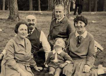 The Liebenau and Olkenitzky families sit on a blanket at the Olkenitzky summer home in Narva Joesuu, Estonia.