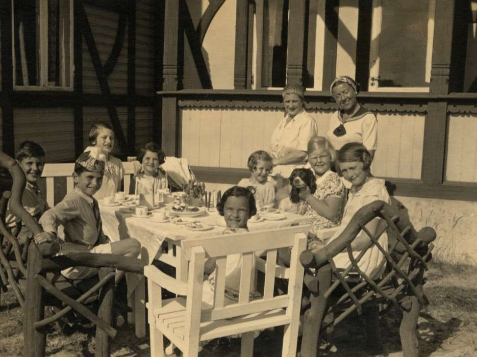 Young children attend a party. Among those pictured are Gerald Liebenau (front left) and his mother Helene (standing far right).