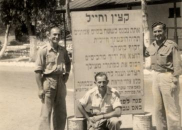 David Bajer and two friends pose next to a sign at an army base in Israel where they were stationed during the War of Independence.