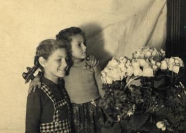Sisters Halina and Eva Litman pose next to a basket of flowers while in hiding in Jaroslaw.