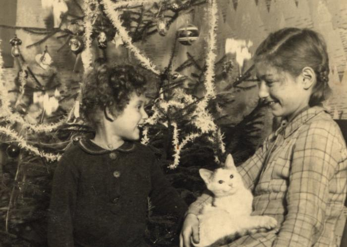 Halina and Eva Litman stand posed next to a Christmas tree while in hiding in Tluste in a washer woman's house.