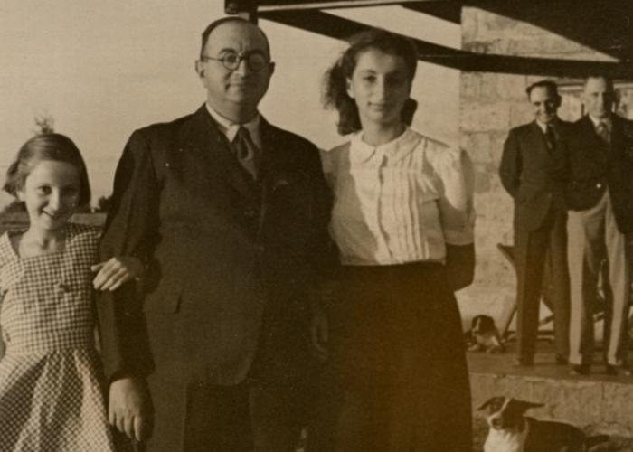 Joseph Berg poses with his two daughters, Gisela and Inge, before the celebration of Passover. In background are Adolf Baum and Mr. Tillingham, who came to the farm for Jewish religious services.